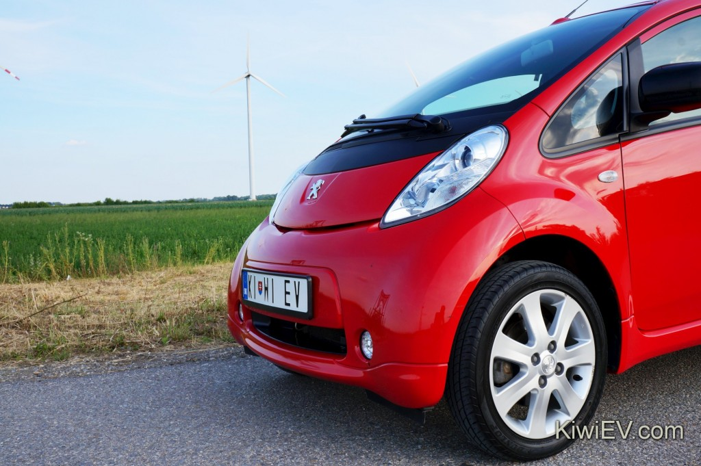 Electric car in front of wind turbine